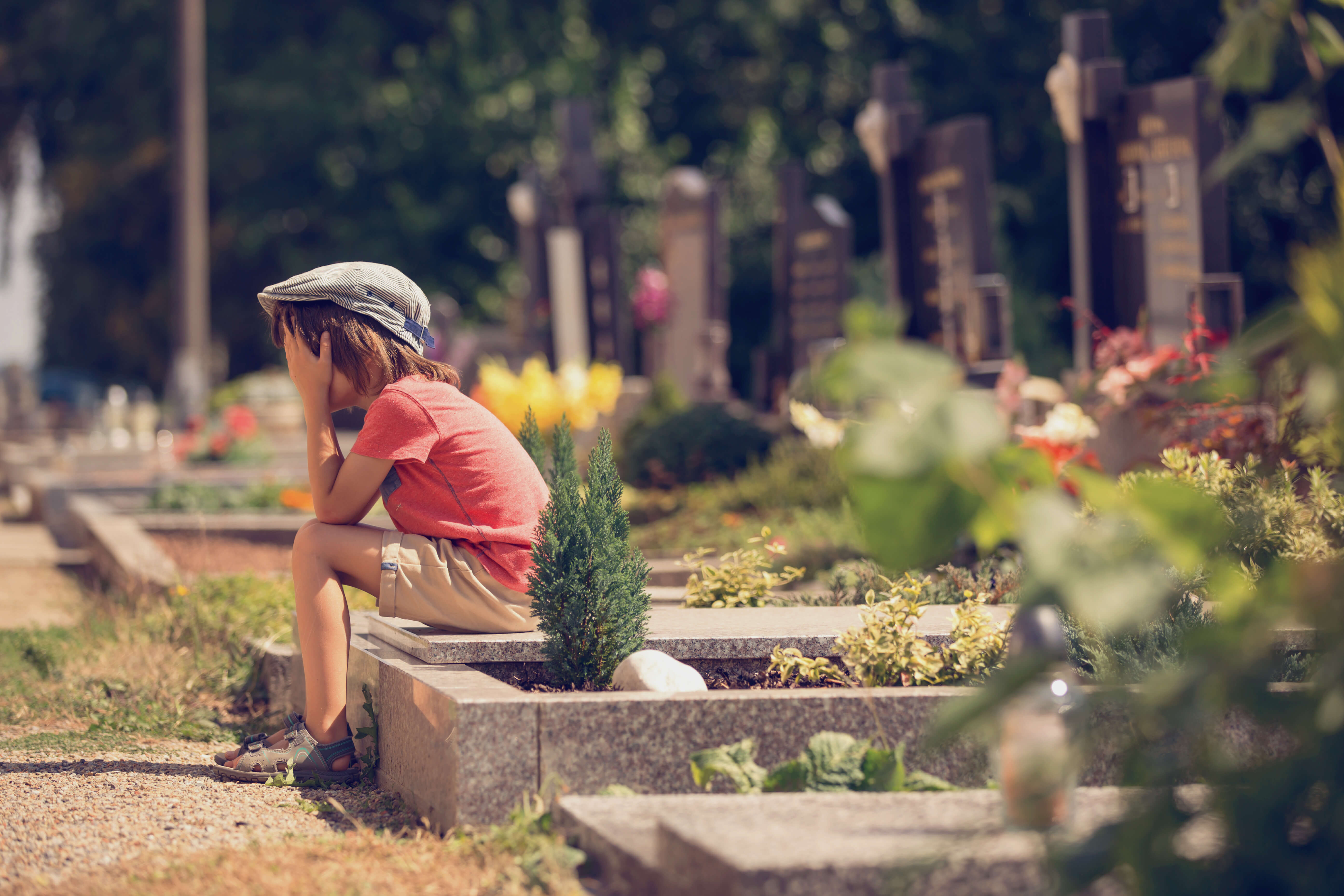 Sad little boy sitting on a grave in a cemetery feeling sad and crying
